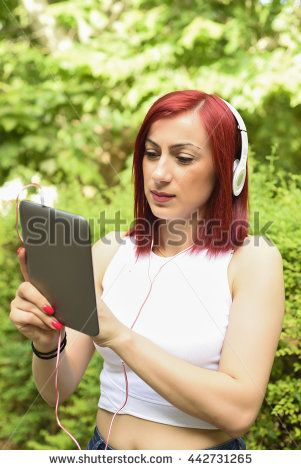 Beautiful young redhead woman browsing a tablet and listening to the music with headphones
