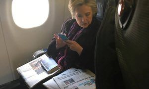 Hillary Clinton looks at a newspaper carrying an article about Vice President Mike Pence's use of personal email.