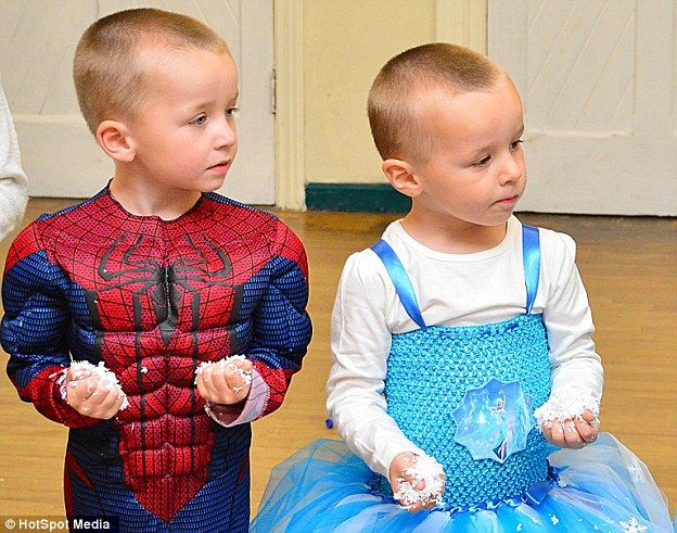 Logan Symonds (right) wearing a blue dress from the Disney film Frozen while standing next to his twin brother Alfie (left). They were photographed celebrating their fourth birthday party. Alfie,dressed as Spider-Man, insisted on having a Frozen themed party so Logan could dress up as Frozen's Princess Elsa