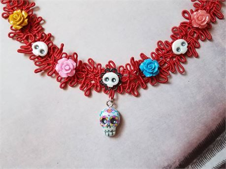 This beautiful little skull and all of its little brothers and sisters dont exist anywhere else. I sculpted the skull and made casts of my master design to be able to paint all of them uniquely. The designs are inspired by traditional art from my hometown in the far south of Mexico. This beautiful red woven choker is adorned by roses of a variety of colors and tiny skulls I designed and made personally. At the center a tiny skull rests on a black filigree base but just below is another…