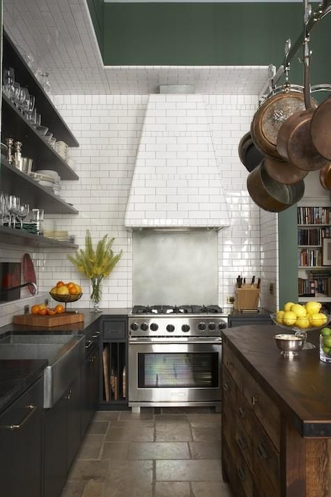 kitchen with subway tile, black cabinets, and reclaimed wood