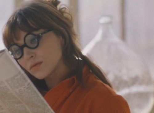 Solid orange sweater with bold circular glasses paired with gentle, tousled hair and pale orange lip.