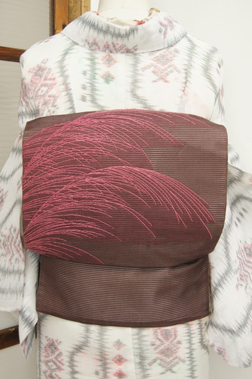 葡萄酒のような、紫みをおびたこっくりと深い赤茶色の地に、さやと風に揺れるような繊細な薄の穂が織り出された絽の夏の名古屋帯です。