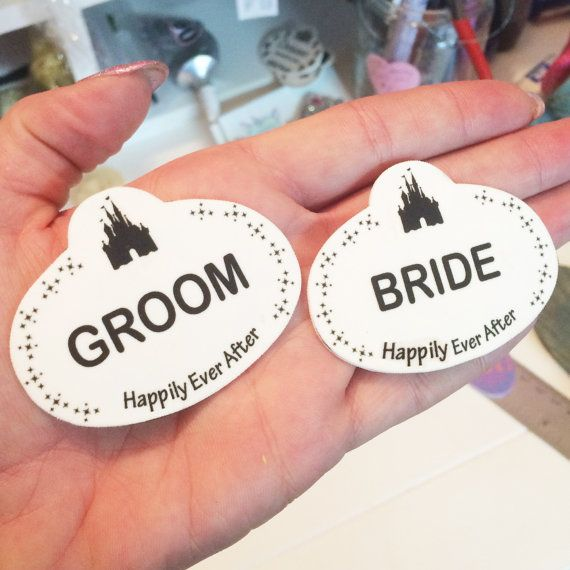 These name badges are inspired by the ones worn by cast members at Disneyland and Walt Disney World. This listing is for 2 tags! One which says Bride and one which says Groom.  Let everyone know that you are a newlywed by wearing our Bride & Groom Disney Inspired Name Tags!!!  A silhouette of the castle is at the top of the name badge. Pixie Dust frames the sides. The name states Bride and Groom. At the Bottom it states Happily Ever After.  Great for your Disney Honeymoon or wedding party…