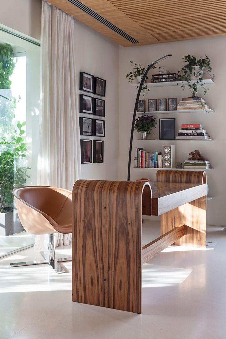 Decoração de apartamento com área verde. No escritório, home office, mesa de madeira, poltrona marrom, luminária de chão, quadros, fotografias, livros, adornos e plantas.