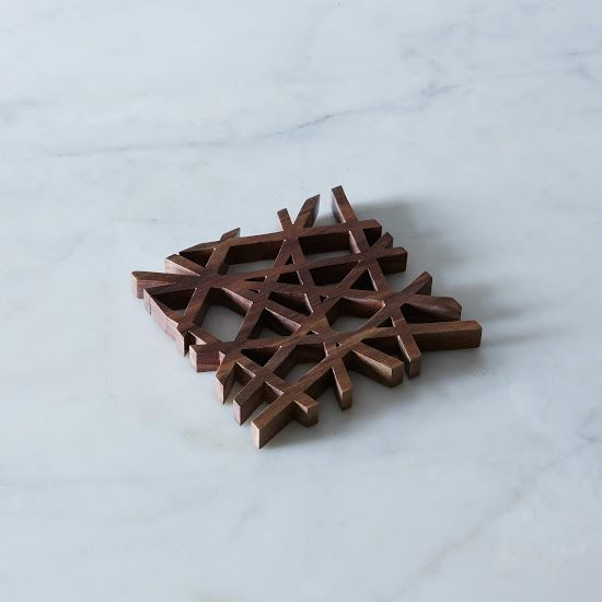 MID-CENTURY MODERN TRIVET Designed by Fredrick Arndt in eco-friendly American black walnut, this trivet is right up our ally. We love the variation in the wood grain pattern and the sleek and structured design. It's a perfect bit of modernity for the table.