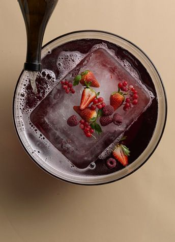 1 cup cube sugar  1 quart sparkling water  1 bottle light, dry red wine  4 oz brandy  2 bottles Champagne  ice block  fruits, for garnish