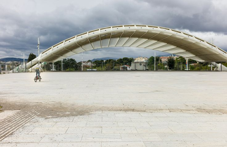 Olympic City Project - OLYMPIC CITIES AFTER THE OLYMPICS - Athens Olympic Sport Complex: A Greek teenager BMX bikes near an archway designed by Santiago Calatrava.