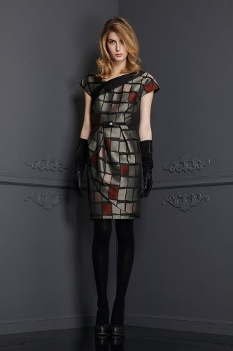 This Italian Jacquard was woven into a geometric collection of squares. The color is a modern blend of Black, Silver and Paprika. Asymmetric in design, flattering placement of the pleated wrap, this dress is perfect for a cocktail look or evening event. Fully Lined. Sizes 2 - 14