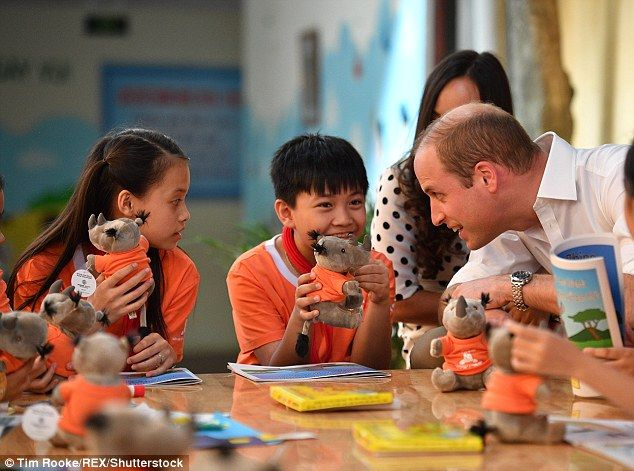 Staying on message: The prince hands over cuddly rhino toys as he discusses the plight of ...