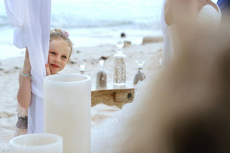 Sweet flower girl looks on as the bride and groom tie the knot in a ceremony on the beach of Tulum at the Nueva Vida de Ramiro boutique hotel. Mexico wedding photographers Del Sol Photography.