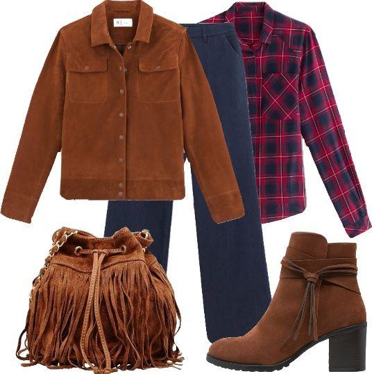 Jeans svasati e camicia a quadri, rossa e blu, abbinati alla giacca in pelle scamosciata, marrone, borsa a spalla, in pelle, con frange e stivaletti in fintapelle, con nappina, color cognac.
