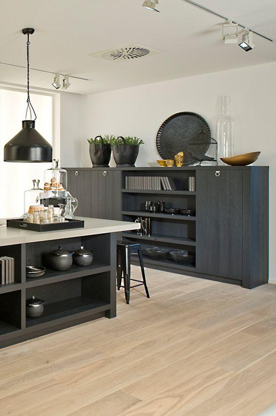 Robuste Küche im Landhausstil. Küchenfronten in Eiche geschwärzt, Metallhocker und die schwarze Industrielampe machen den Fabrik Chic aus