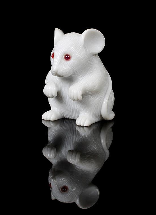 <b>A Carved Dolomite and Ruby Mouse,</b> <br  /> Idar-Oberstein, Germany, <br  /> carved in a whimsical style to depict a standing mouse from white Dolomite from the Italian Alps, the surface textured to mimic fur with inset ruby eyes. <br  /> Heights: 4.40 cm. <br  />