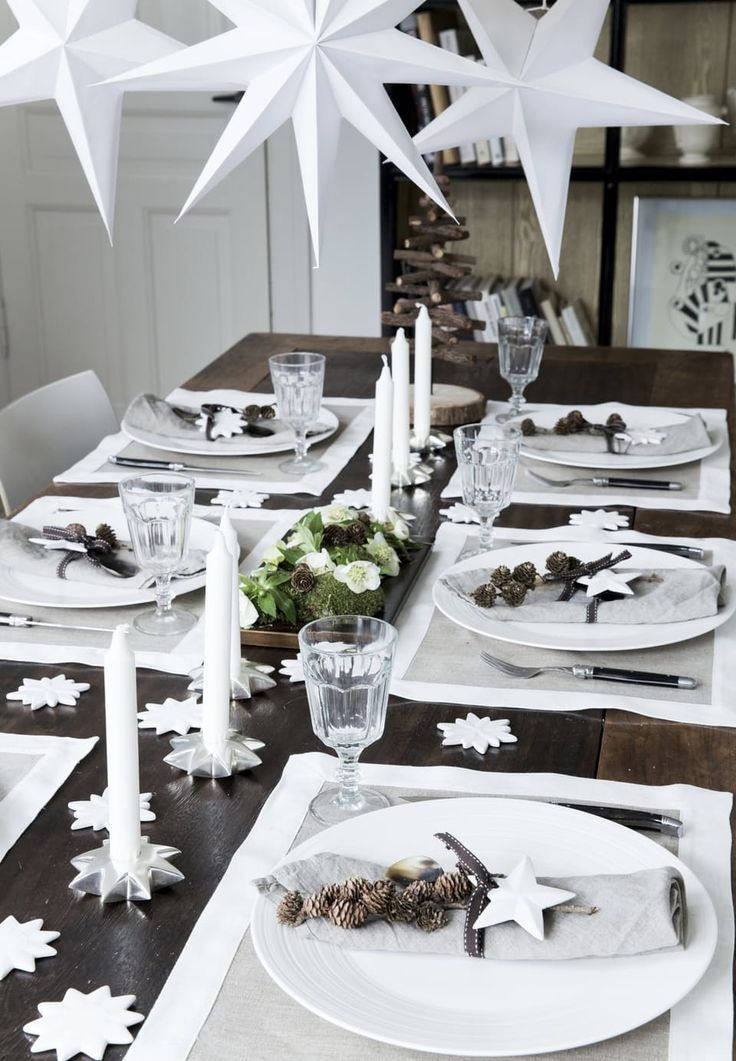Amazing Christmas table setting with candles and white stars as decorations. We love the pretty napkins with small cones.