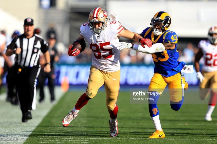 News Photo : George Kittle of the San Francisco 49ers eludes...