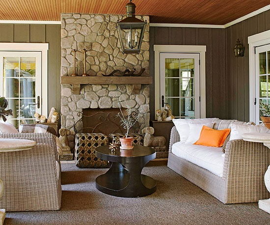 Color Story_Wicker furniture in driftwood-inspired hues echoes the look of the focal point fireplace surround on this porch. The traditional wicker furnishings get a boost of modernity thanks to crisp white seat cushions and striking orange accents. An iron lantern hung above the seating area helps illuminate the space after the sun goes down.