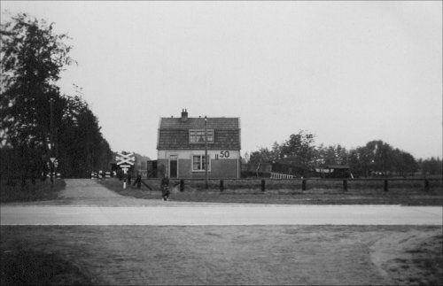"""De onbewaakte overweg aan de Stoutenburgerlaan met de dienstwoning """"blokpost 50"""". De foto is genomen rond 1937 door J.A.W. Vinju, schoonzoon van Aart van de Pol die tussen 1905 en 1910 de blokwachter van blokpost 50 is geweest. Deze dienstwoning stond aan het einde van het zuidelijk perron van station Hoevelaken. De foto is vanuit het noorden genomen. Dwars op de foto zien we de oude Rijksweg Amersfoort-Apeldoorn.Deze onbewaakte overweg stond bekend als onveilig"""