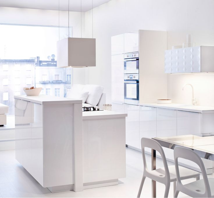 View of the whole IKEA kitchen, in brilliant white. Cabinets, dining area, appliances and light.