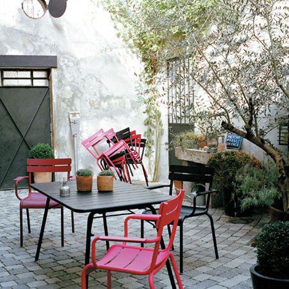 Un petit patio aménagé avec une table et des chaises colorées