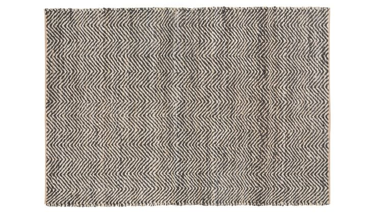 Striking zig-zag pattern and thick hand woven natural fibres give this traditionally crafted Chevron Jute rug a spike of contemporary style. The sharp parallels of the chevron design contrasts dark black lines and greyish tones of jute, which, on close inspection, reveal the chunky interwoven threads that make this pleasing design.