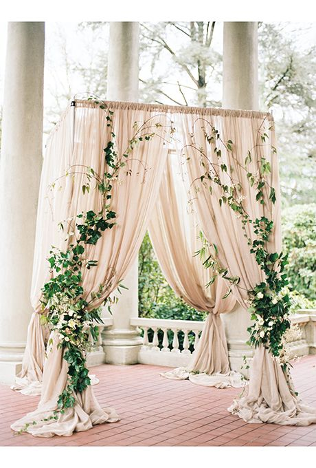 Brides.com: . Billowing taupe drapes adorned with climbing ivy make for a romantically dramatic ceremony arbor.