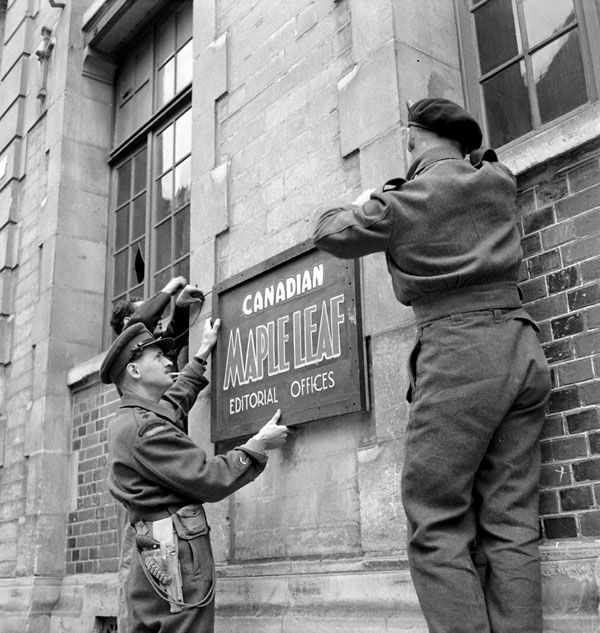 """Lieutenant-Colonel Richard """"Dick"""" Sankey Malone (left) helping to erect the sign at the editorial office of the Maple Leaf newspaper, at la Presse Caennaise, 34 Rue Demolombe, Caen, France, 11 July 1944. LAC negative PA-131395 MIKAN 3358137"""