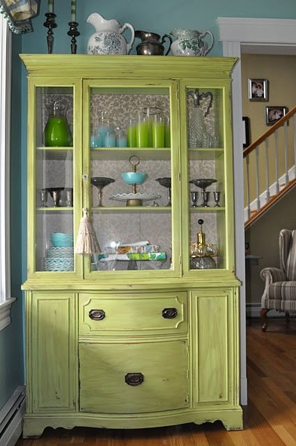 Love this green china cabinet and the aqua and green dishes inside.