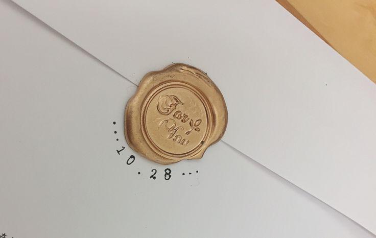 ダイソーのシーリングワックスに セリアのシーリングスタンプに キャンドゥのゴールドスプレーで 出来上がったシーリングスタンプに セリアの自分で組み合わせられる丸型スタンプで下には日付と、これにはのせなかったけど上には2人の名前がくるようにしました
