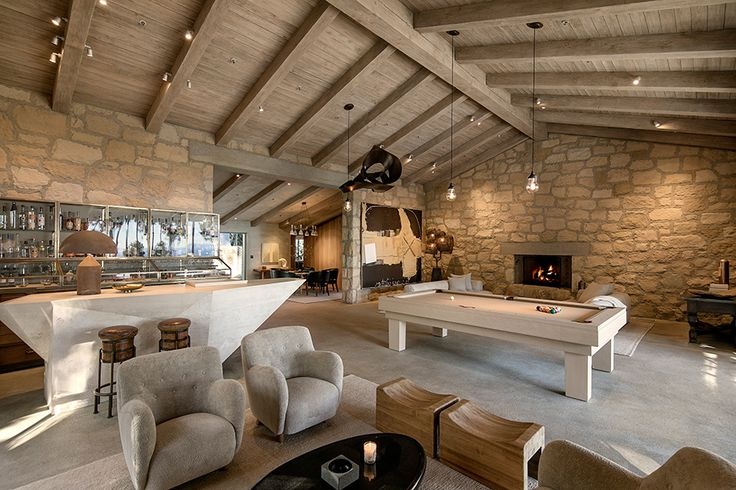 Ellen DeGeneres and Portia de Rossi's Romantic Santa Barbara Villa | A warming fireplace with a natural hearth and concrete mantel is cut into one arresting stone wall. Above, sculpture and lanterns are suspended from the soaring ceiling. The modern stone bar cuts a striking silhouette and is backed by a vintage apothecary chest offering bronze and glass bar display cases.