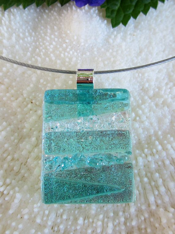 This beautiful aquamarine art glass pendant is fused of pieces transparent sea green glass and clear and sea green frit on silver dichroic base.