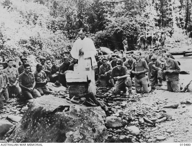 New Guinnea, Mount Tambu fighting. Within sound of rifle, artillery and mortar fire, Chaplain Patrick (Theo) O'Keefe of Headquarters, 17th Brigade, holds mass alongside a stream at the foot of Mount Tambu, 10 Aug 1943.