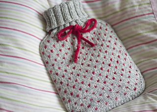 A classic hot water bottle cosy knit in stocking stitch and finished with an elastic collar in rib.