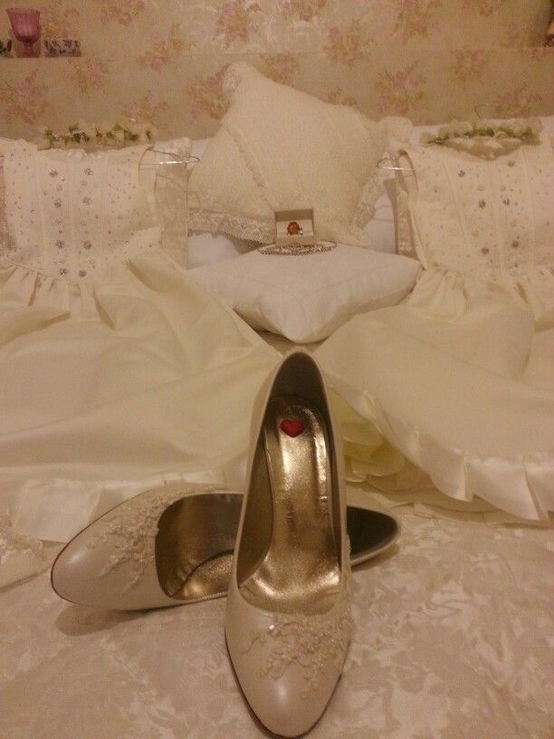 The dresses for my flower girls  and my shoes , on our wedding bed.