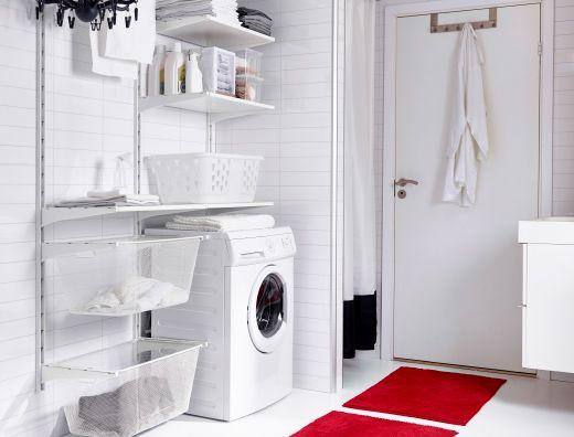 Ambiente di servizio con scaffali bianchi, contenitori di diverse dimensioni e stendibiancheria.
