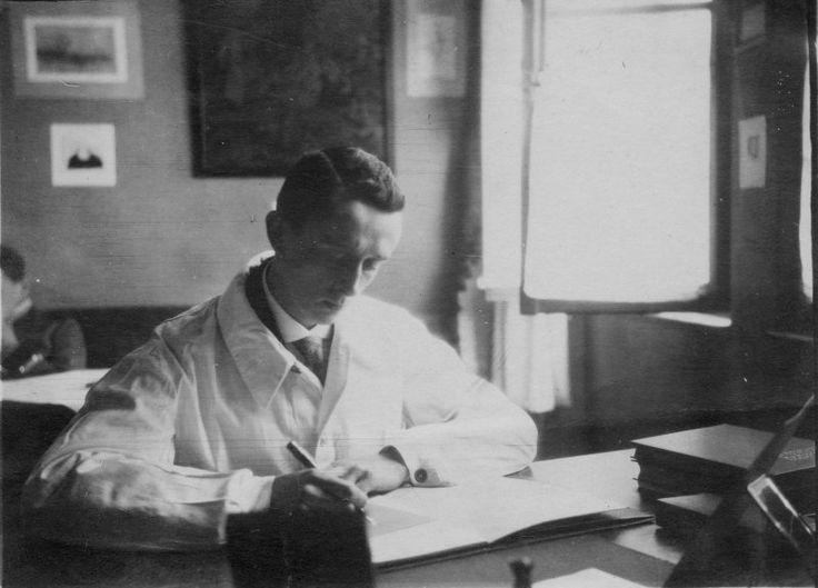 Mann im weißen Kittel am Schreibtisch, 1920er
