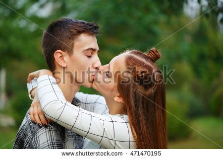 Loving couple teens kiss passionately. Girlfriend and boyfriend together. Close-up. First love. He falls in love. Date. First kiss