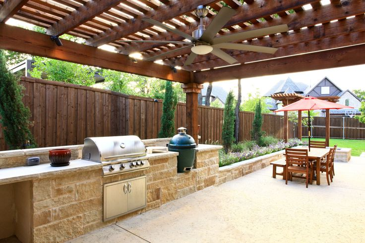 Complete outdoor kitchen with BBQ and green egg built into stone countertops. By Outdoor Signature in Argyle, TX.