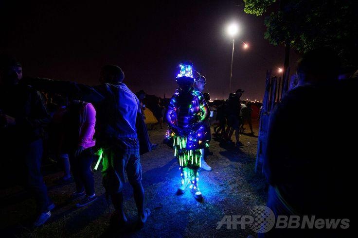 英南西部サマセット(Somerset)州ピルトン(Pilton)で開幕した世界最大級の野外音楽祭典「グラストンベリー・フェスティバル(Glastonbury Festival)」の会場で、電飾で飾った衣装を着た参加者(2014年6月25日撮影)。(c)AFP/LEON NEAL ▼27Jun2014AFP|世界最大の英野外音楽祭「グラストンベリー」が開幕 http://www.afpbb.com/articles/-/3018900 #Glastonbury_Festival