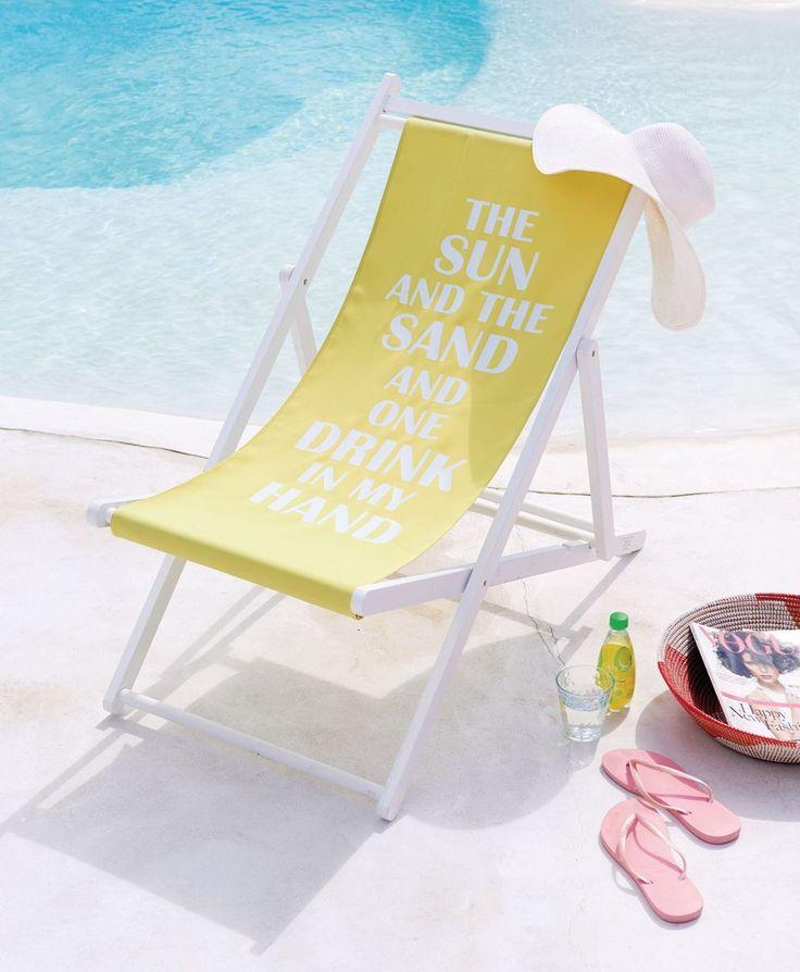 """Die Sonne und der Sand und ein Drink in meiner Hand! Auf diesem Liegestuhl mit weiß lackiertem Gestell und grün-gelber Sitzfläche ist in Weiß der Schriftzug """"The sun and the sand and one drink in my hand"""" aufgedruckt. Perfekt für einen entspannten Tag am Strand, auf der Terrasse oder im Garten"""