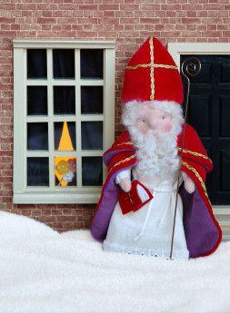 """Ontwerp van """"Atelier Anemoontje"""". Sinterklaas is ongeveer 15 cm. hoog en gemaakt van mooie rode nicky velours. De mantel en de pelerine zijn gevoerd met paars flanel. Pakketje is compleet met goud kleurige staf. Dit pakketje is te maken door de ervaren poppenmaakster."""