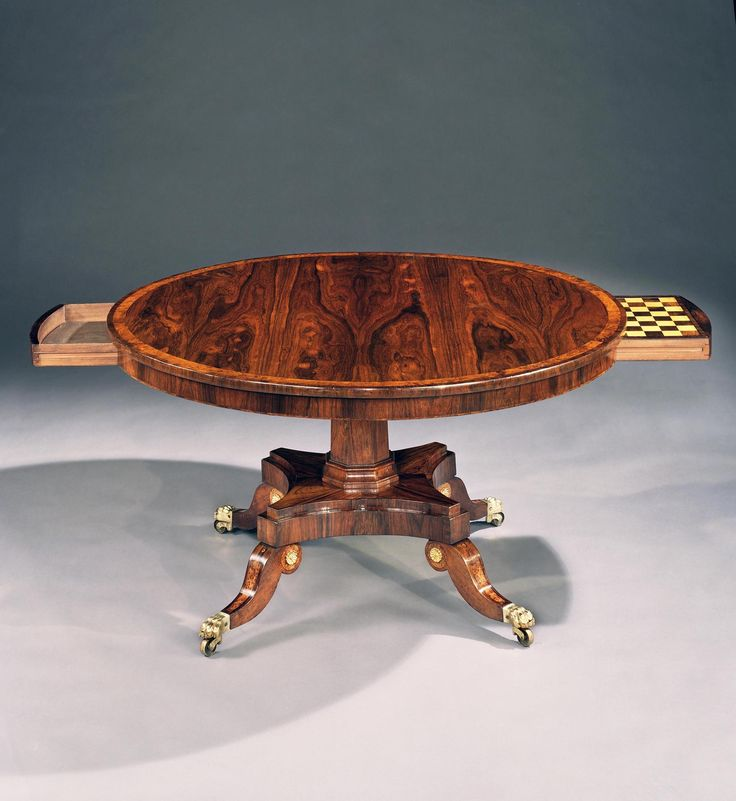 A most unusual early 19th century Regency rosewood circular breakfast table. The circular tilt-top banded in burr yew and fitted with two drawers, one concealing a chess and backgammon board; on an octagonal faceted column and four way stepped platform with concave sides issuing in splay legs with yew wood inlay and terminating in brass paw castors