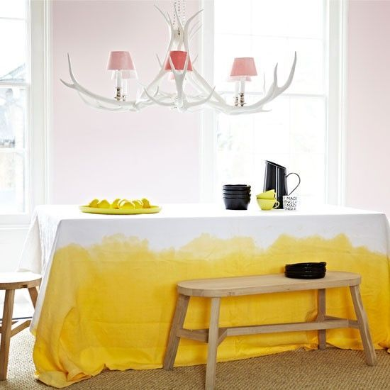 Dining room with yellow accents  A bright-yellow, dip-dyed tablecloth and show-stopping chandelier pack a punch in this quirky dining room. The contrast between white-washed furniture and soothing pinks, and buttercup yellow, means this scheme is bound to impress.