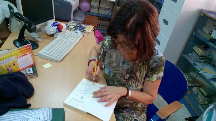 Ana Alcolea firmando libros en la reunión de los clubes de lectura de 1º y 2º con Ana Alcolea en la biblioteca escolar