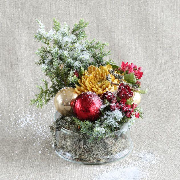 Небольшая композиция из тщательно подобранных цветов, декоративной зелени и декора станет изящным подарком коллегам, друзьям и просто милым сердцу людям. Собранная на контрасте фактур, она поражает удивительным сочетанием махровой хризантемы, соцветий бовардии, хвои можжевельника, густо припорошенной снегом.