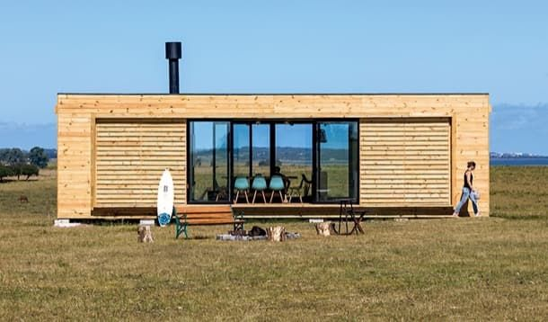 RJI: casa prefabricada en Uruguay. El estudio de arquitectura MAPA diseñó la casa industrializada RJI, ubicada en un sitio remoto de Uruguay. Está compuesta por dos módulos de madera. El proyecto se construyó en un taller, y luego de transportó al sitio en camión. Una grúa la puso sobre unos micro-pilotes. Planos y fotos del edificio. #CasasPrefabricadas