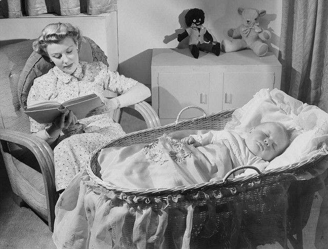 Moeder leest terwijl de baby slaapt.