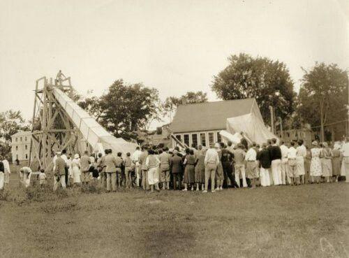 """Zonsverduistering van 30 augustus 1932 in Fryeburg, Maine, Verenigde Staten van Amerika. Foto: Overzicht van het """"eclips-kamp"""" op het terrein van de universiteit van Michigan. Toeschouwers staan rond de naar boven gerichte reusachtige camera, waarmee men de zonsverduistering kan volgen."""