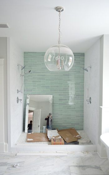 Those bluey-green glass tiles are this 3 x 12″ New Haven tile and the sides are 3 x 6″ white subway tiles, both donated by The Tile Shop. Here's a shot from back in December (!!) when we picked it out. The tub flooring is the one in the background of this tile shot, which is their Evanston series in Frost Snow. The little glass squares mixed with marble help tie everything in the room together | Young House Love