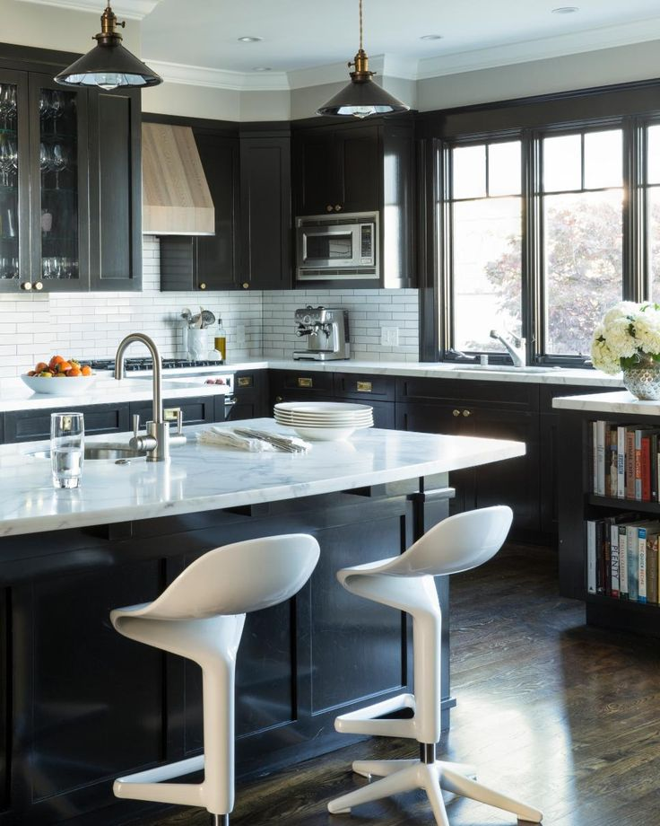 This transitional kitchen feels classic due in part to its black and white color palette but utilizes modern touches like high end appliances and modern style seating.